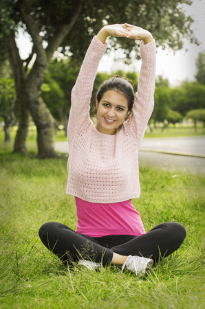 arms above head: Hispanic brunette in yoga clothes sitting on grass with legs crossed and stretching both arms above head smiling to camera.