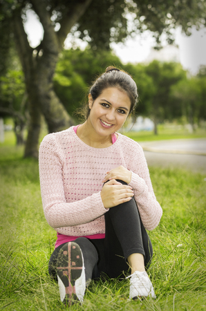looking towards camera: Hispanic brunette sitting on grass in yoga clothing left knee bent with arms wrapped around looking towards camera smiling..