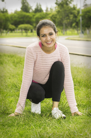 starting position: Hispanic brunette model in park with yoga clothes doing starting position pose for camera. Stock Photo