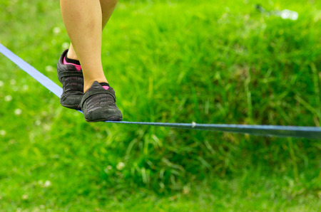 slack: Closeup womans feet with shoes balancing a tightrope or slackline and grassy background.