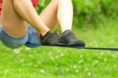 spread legs: Closeup of womans legs spread out with shoes sitting on tightrope or slackline and grassy background.