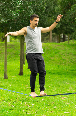maintaining: Man walking on slackline in park with arms out maintaining balance and concentrated. Stock Photo