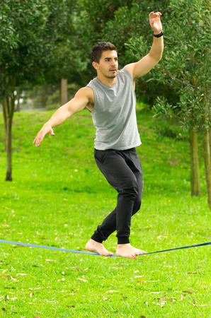 arms out: Man walking barefoot on slackline in park with arms out and deep concentrated facial expression. Stock Photo