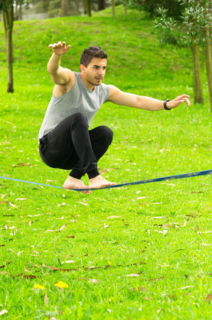 bended: Man sitting with bended knees on slackline in park environment. Stock Photo