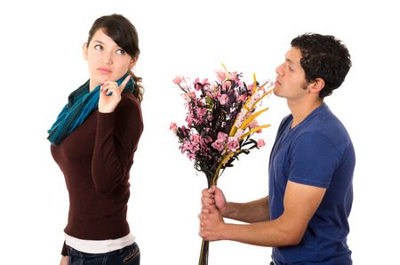 recieving: Hispanic couple fighting as man attempts to give girlfriend flowers but she gives him cold shoulder attitude looking backwards with finger up in air.