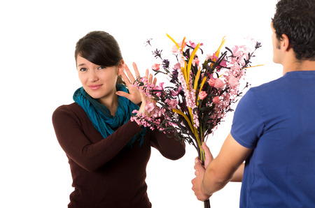 gullible: Hispanic couple fighting as man tries to give girlfriend flowers while she pushes them away with annoyed facial expression.
