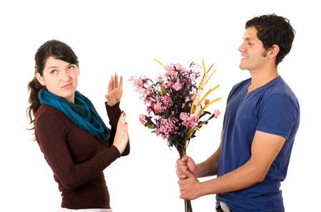 insulted: Man tries to give girlfriend flowers but she dimsisses him by holding up her hand and looking upset.