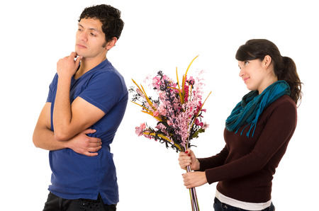 Woman holding flowers up behind mans back with hopeful expression and man expressing dismissive attitude.