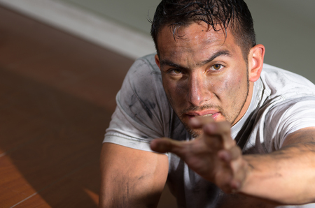 desperately: Hispanic man with dirty face and shirt lying on floor looking desperately to camera reaching left hand towards lens. Stock Photo