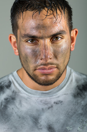 Hispanic man with dirty face and shirt looking to camera serious facial expression.
