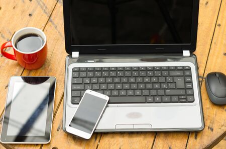 laptop mobile: Wooden table with open laptop, mobile, tablet and red coffee mug.