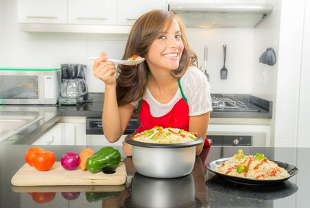 Hispanic beautiful woman cooking in modern kitchen bending over counter holding up spoon of food and smiling to camera.