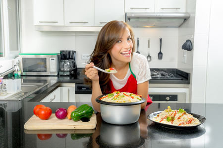 Hispanic beautiful woman cooking in modern kitchen bending over counter holding up spoon of food and smiling to camera with toungue out.