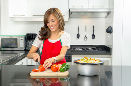 Hispanic beautiful woman cooking in modern kitchen smiling happily while cutting a tomato on wooden board with other vegetables visible next to pot of food. Banque d'images