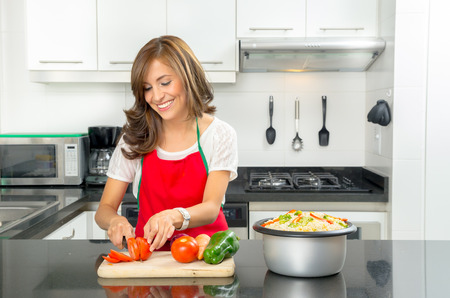 Hispanic beautiful woman cooking in modern kitchen smiling happily while cutting a tomato on wooden board with other vegetables visible next to pot of food. Archivio Fotografico
