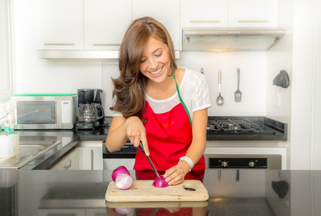 Beautiful woman cooking in modern kitchen chopping onions and laughing.