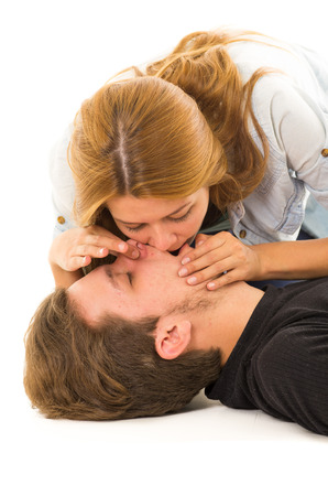 Couple demonstrating first aid techniques with woman performing mouth resuscitation. Stock Photo