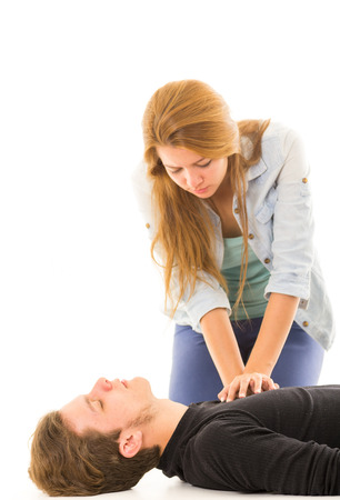 Couple demonstrating first aid techniques with woman applying cpr on male pattient lying down.