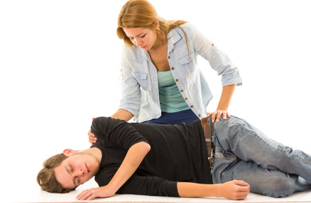 Couple demonstrating first aid techniques with male patient lying in recovery position and female sitting above him. Banque d'images