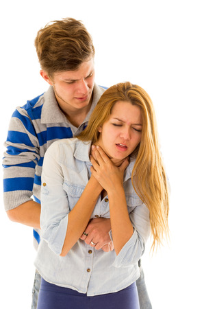 choking: Couple demonstrating first aid techniques by man performing heimlich on female choking.