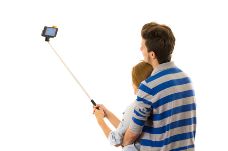 shot from behind: Couple with selfie stick embracing and posing for mobile shot from behind side angle.