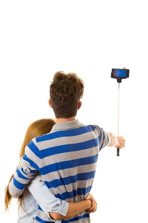 facing on camera: Couple with selfie stick posing for mobile back facing camera.
