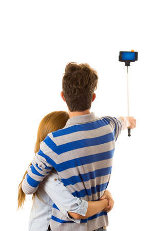 couple back to back: Couple with selfie stick posing for mobile back facing camera.