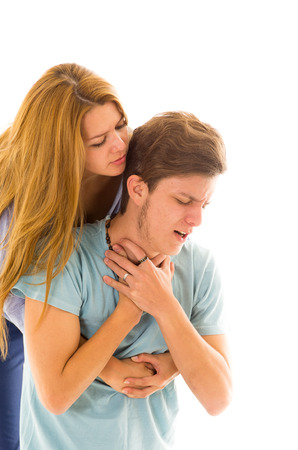 maneuver: Couple demonstrating first aid procedure for abdominal thrusts, Heimlich Manoeuvre or Maneuver to treat man choking by foreign objects