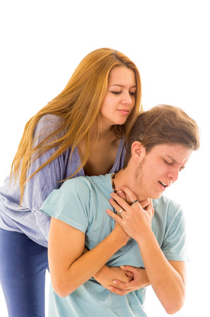 manoeuvre: Couple demonstrating first aid procedure for abdominal thrusts, Heimlich Manoeuvre or Maneuver to treat man choking by foreign objects