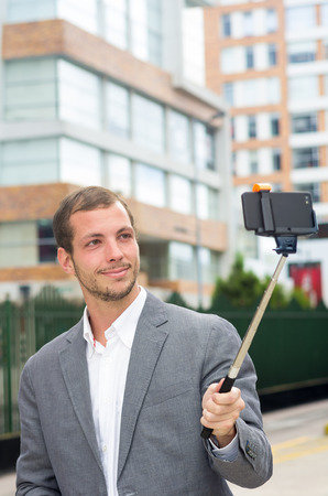 formal clothing: Man formal clothing posing with selfie stick in urban environment. Stock Photo