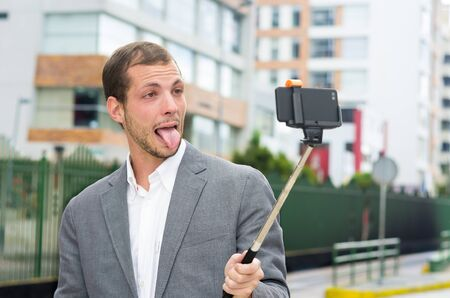 formal clothing: Man in formal clothing posing with selfie stick in urban environment showing tongue.