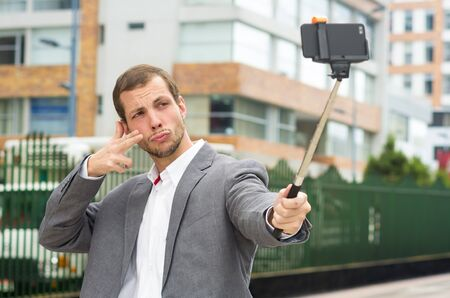 Man wearing formal clothing posing with selfie stick in urban environment using right hand to make a signal.