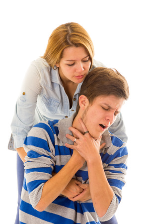 choking: Couple demonstrating first aid techniques with woman performing heimlich in male choking.