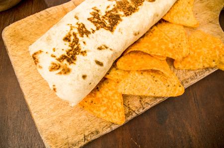 burrito: Chicken wrap burrito served on a wooden plate