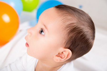 surprised baby: cute surprised baby boy looking left in white background with colorful ballons Stock Photo