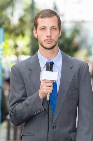 live work city: Attractive professional male news reporter wearing grey suit holding microphone, talking to camera from urban setting. Stock Photo