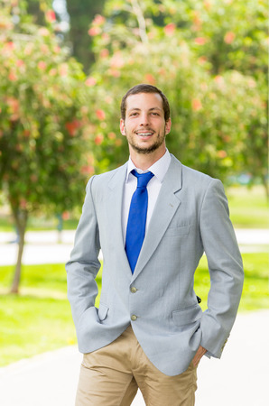 live work city: Handsome successful businessman professional in grey suit posing for camera at the park. Stock Photo