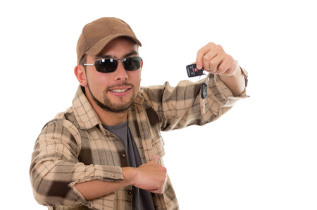 flannel: happy young guy in flannel shirt and cap showing car keys in his hand isolated on white