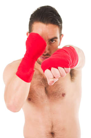 red shorts: young martial arts fighter wearing red shorts and wristband punching isolated on white