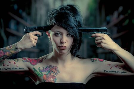 provocative: provocative tattooed girl poiting guns to her head looking at camera