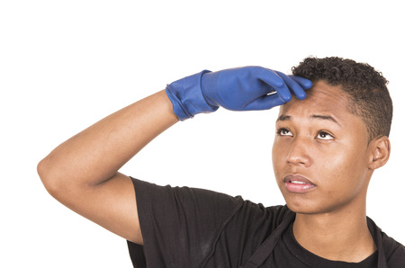 facing to camera: Closeup hispanic young man wearing blue cleaning gloves facing camera with right arm raised.