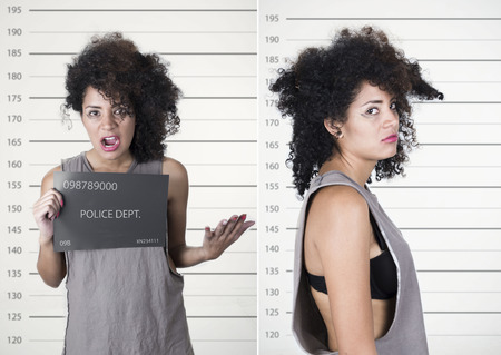 disobedient: Hispanic brunette model afro like hair wearing grey sleeveless shirt holding up police department board with number as posing for mugshot concept, front and profile angles.