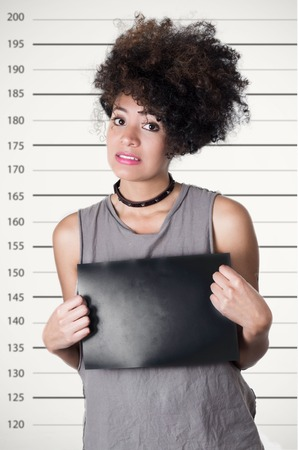 mugshot: Hispanic brunette rebel model with afro like hair wearing grey sleeveless shirt holding up blank board as posing for mugshot, guilty facial expression. Stock Photo