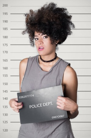 Hispanic brunette rebel model afro like hair wearing grey sleeveless shirt holding up police department board with number as posing for mugshot, careless facial expression.