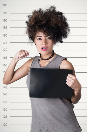 simulating: Hispanic brunette rebel model with afro like hair wearing grey sleeveless shirt holding up blank board as posing for mugshot concept, lifting one arm simulating punch.