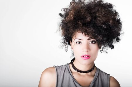headshot: Headshot brunette hispanic model afro like hair dark eyes black necklace posing for camera. Stock Photo