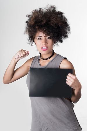 to rebel: Hispanic brunette rebel model with afro like hair wearing grey sleeveless shirt holding up blank board as posing for mugshot concept, lifting one arm simulating punch.