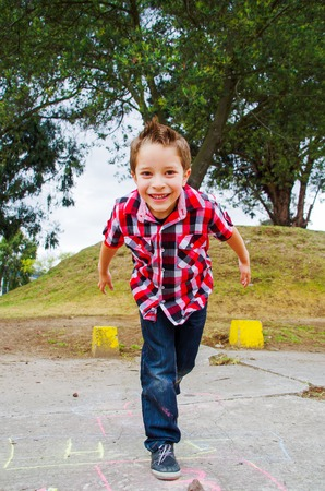 hopscotch: cute happy boy playing hopscotch in the park Stock Photo