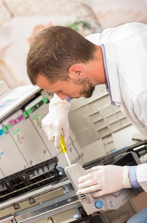 close-up shot jonge mannelijke technicus repareren van digitale fotocopier machine