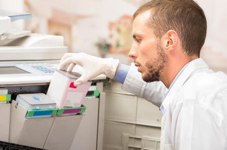 fotocopiadora: disparo de cerca de técnico varón joven cambiando de color cartucho de tóner en la máquina copiadora digital